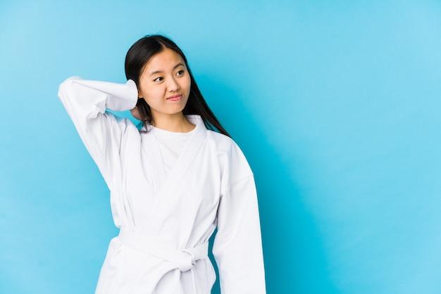 Junge chinesische frau, die karate praktiziert, isolierte berührung des hinterkopfes, denken und treffen einer wahl.