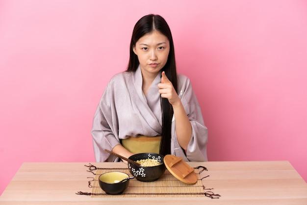 Junge chinesische frau, die kimono trägt und frustrierte nudeln isst und nach vorne zeigt