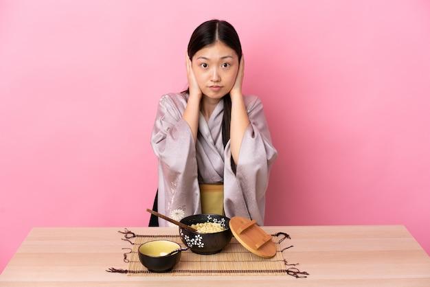 Junge chinesische frau, die kimono trägt und frustrierte nudeln isst und ohren kegelt