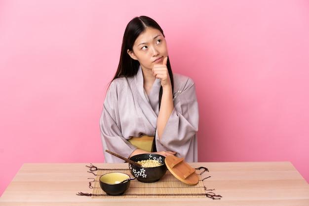 Junge chinesische frau, die kimono trägt und nudeln isst, die zweifel haben