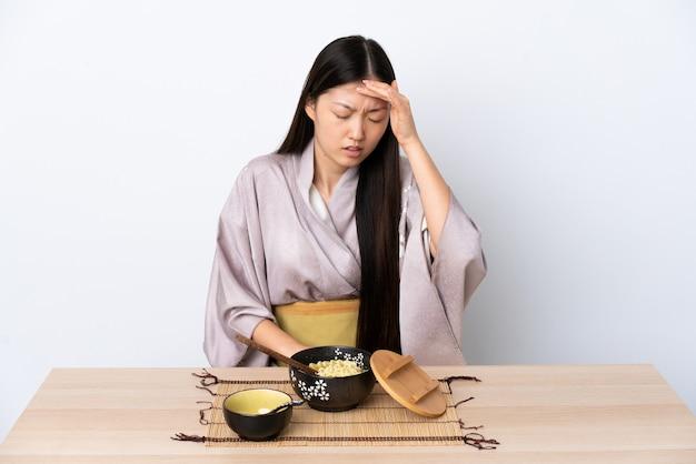 Junge chinesische frau, die kimono trägt und nudeln mit kopfschmerzen isst