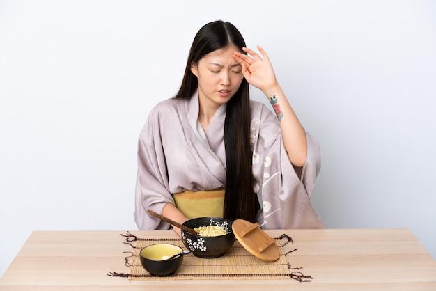 Junge chinesische frau, die kimono trägt und nudeln mit müde und krankem ausdruck isst