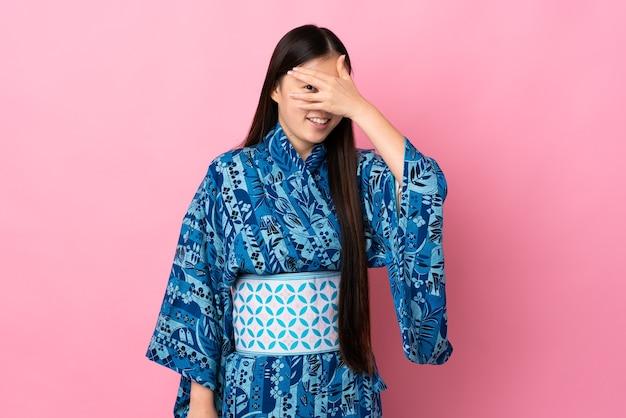 Junge chinesische frau, die kimonokegelaugen durch hände trägt und lächelt