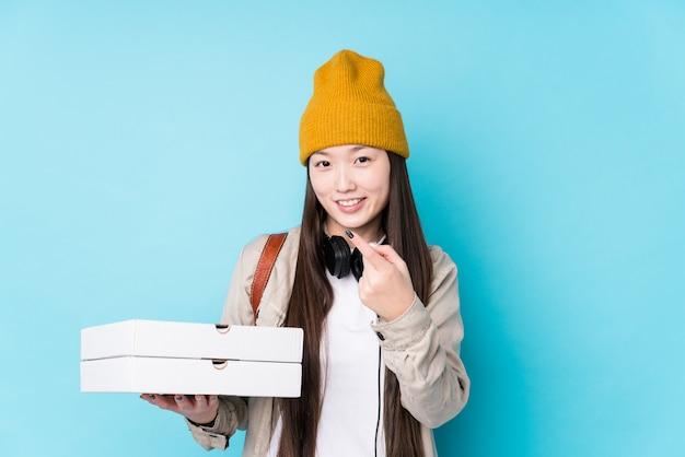 Junge chinesische frau, die lokal gehaltene pizzen hält, zeigt mit dem finger auf sie, als ob die einladung näher kommt.