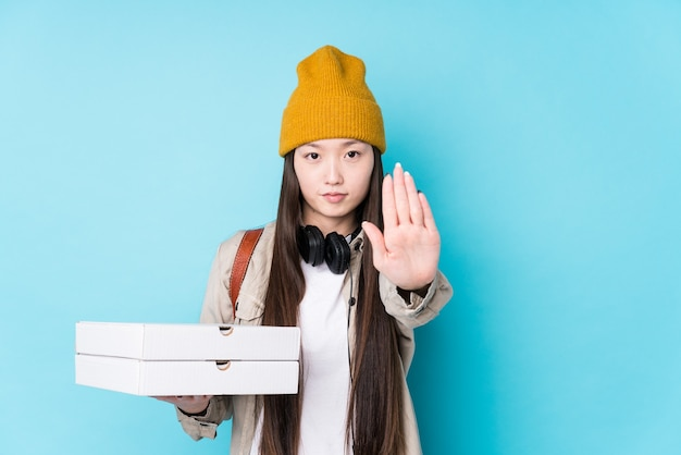 Junge chinesische frau, die pizzas lokalisiert hält, die mit ausgestreckter hand stehen, die stoppschild zeigt, das sie verhindert.