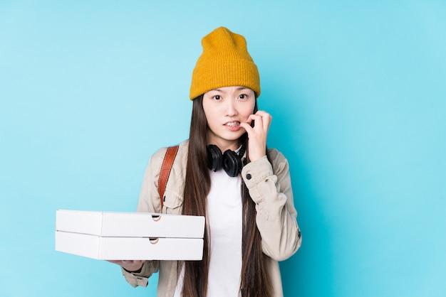 Junge chinesische frau, die pizzen hält, die fingernägel beißen, nervös und sehr ängstlich.