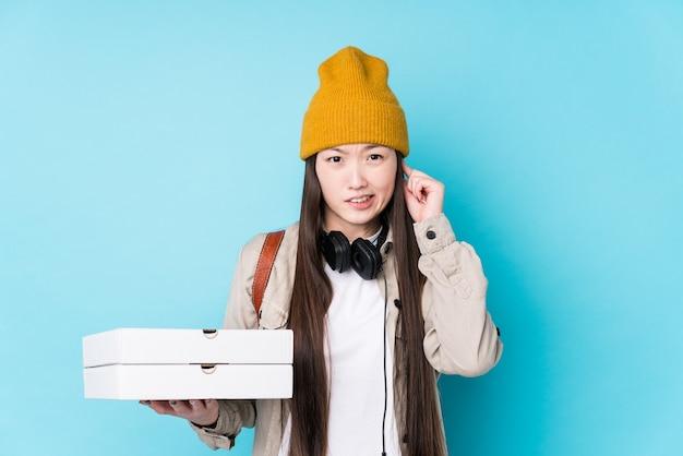 Junge chinesische frau, die pizzen lokalisiert hält, die ohren mit händen bedeckt.