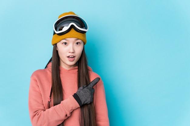 Junge chinesische frau, die skibekleidung isoliert zeigt, zeigt zur seite