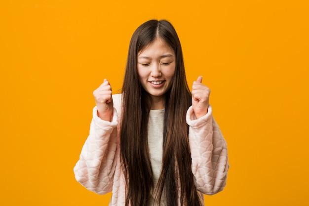 Junge chinesische frau im pyjama, der faust anhebt, glücklich und erfolgreich sich fühlt. sieg.