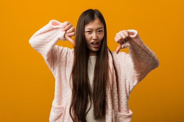 Junge chinesische frau im pyjama, der unten daumen zeigt und abneigung ausdrückt.
