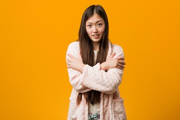 Junge chinesische frau im pyjama, der wegen der niedrigen temperatur oder einer krankheit kalt geht.