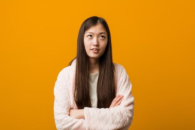 Junge chinesische frau im pyjama ermüdete von einer sich wiederholenden aufgabe.