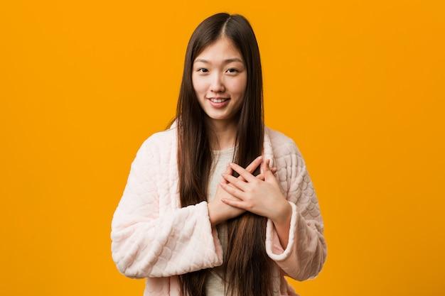 Junge chinesische frau im pyjama hat den freundlichen ausdruck und drückt palme zur brust. liebe .