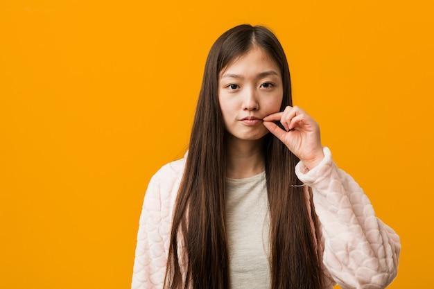 Junge chinesische frau im pyjama mit den fingern auf den lippen, die ein geheimnis halten.