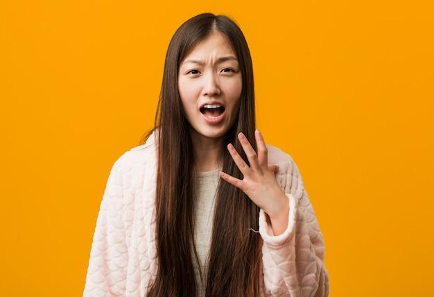 Junge chinesische frau im pyjama schreiend mit raserei.
