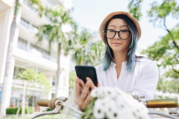 Junge chinesische frau in den gläsern, die lippen schmollen und soziale medien über smartphone überprüfen