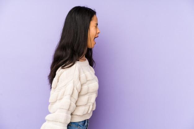 Junge chinesische frau lokalisiert auf einem lila hintergrund, der in richtung eines kopienraums schreit