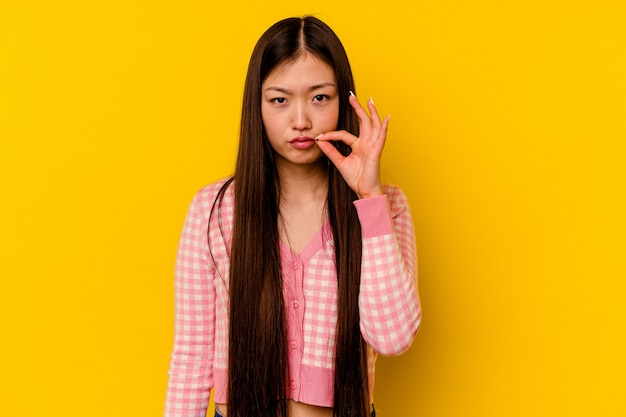 Junge chinesische frau lokalisiert auf gelb mit den fingern auf den lippen, die ein geheimnis halten.