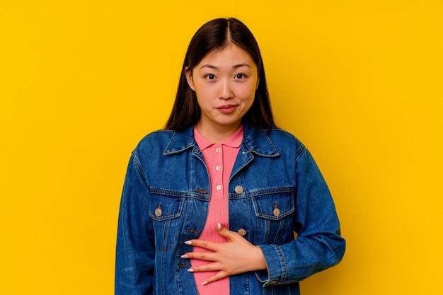 Junge chinesische frau lokalisiert auf gelbem hintergrund berührt bauch, lächelt sanft, ess- und zufriedenheitskonzept.