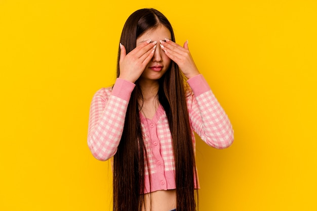 Junge chinesische frau lokalisiert auf gelbem hintergrund fürchtet, augen mit händen zu bedecken.