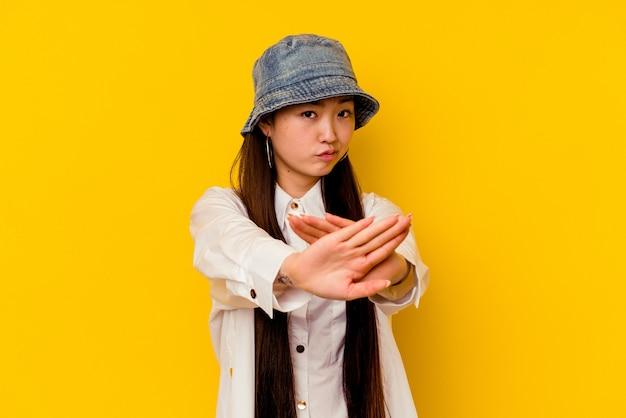 Junge chinesische frau lokalisiert auf gelber wand, die eine verweigerungsgeste tut