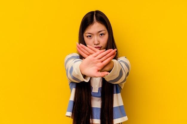 Junge chinesische frau lokalisiert auf gelber wand stehend mit ausgestreckter hand, die stoppschild zeigt, das sie verhindert.