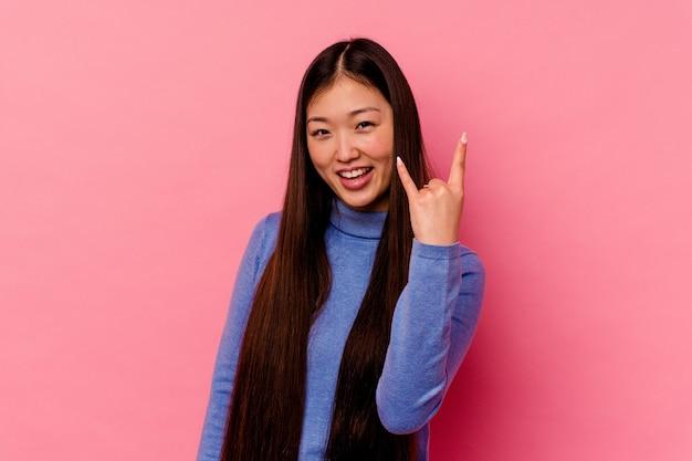Junge chinesische frau lokalisiert auf rosa hintergrund, der felsengeste mit den fingern zeigt