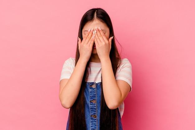 Junge chinesische frau lokalisiert auf rosa wand angst, augen mit händen zu bedecken.