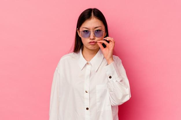 Junge chinesische frau lokalisiert auf rosa wand mit den fingern auf den lippen, die ein geheimnis halten.