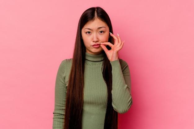Junge chinesische frau lokalisiert auf rosa wand mit den fingern auf den lippen, die ein geheimnis halten