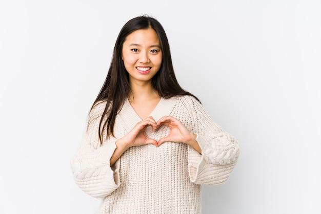 Junge chinesische frau lokalisierte das lächeln und das zeigen einer herzform mit den händen.