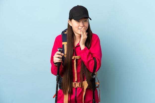 Junge chinesische frau mit rucksack und wanderstöcken über isolierte blaue wand glücklich und lächelnd, die mund mit händen bedeckt