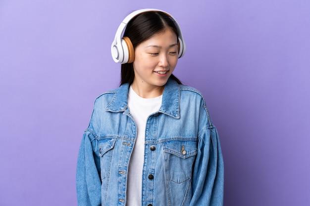 Junge chinesische frau über isolierte lila hörende musik