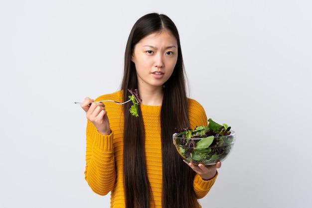 Junge chinesische frau über isolierte weiße wand, die eine schüssel salat mit traurigem ausdruck hält