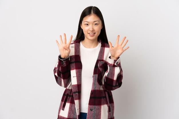 Junge chinesische frau über isolierte weiße wand, die neun mit den fingern zählt