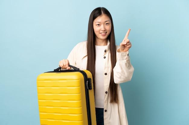 Junge chinesische frau über isolierter wand im urlaub mit reisekoffer und zählen eines