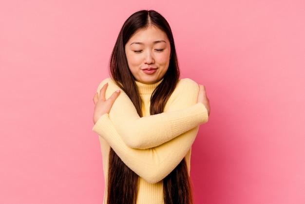 Junge chinesische frau umarmt, lächelt sorglos und glücklich.