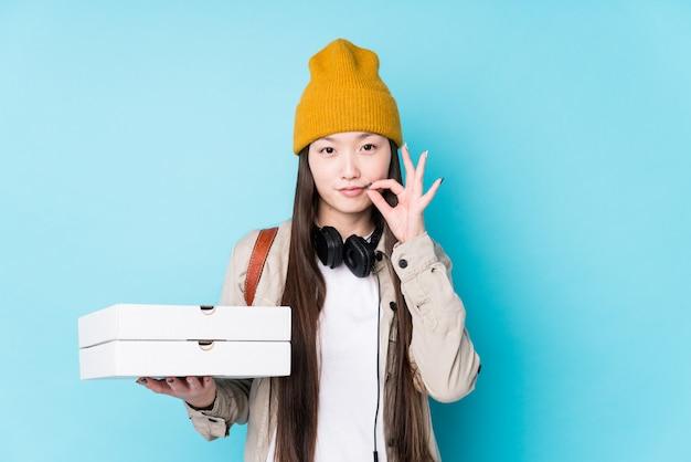 Junge chinesische frau, welche die pizzas lokalisiert mit den fingern auf den lippen halten ein geheimnis hält.
