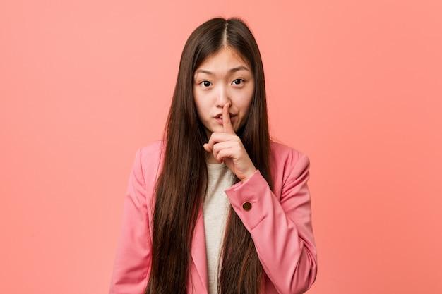 Junge chinesische geschäftsfrau, die den rosa anzug hält ein geheimnis oder bittet um ruhe trägt.