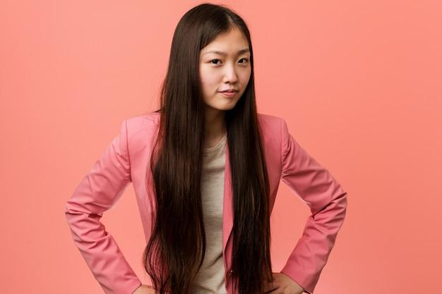 Junge chinesische geschäftsfrau, die den rosa anzug schilt jemand trägt, das sehr verärgert ist