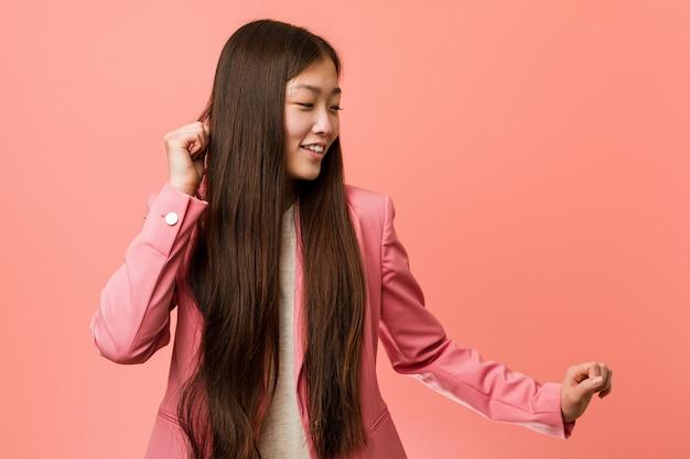 Junge chinesische geschäftsfrau, die den rosa anzug tanzt und spaß hat.