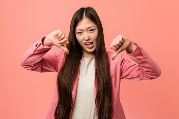 Junge chinesische geschäftsfrau, die den rosa anzug unten zeigt daumen und abneigung ausdrückt trägt.