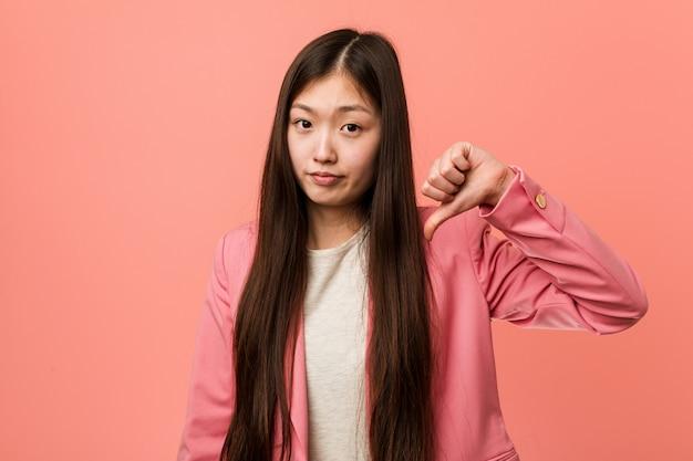 Junge chinesische geschäftsfrau, die den rosa anzug zeigt eine abneigungsgeste, daumen unten trägt. uneinigkeit konzept.