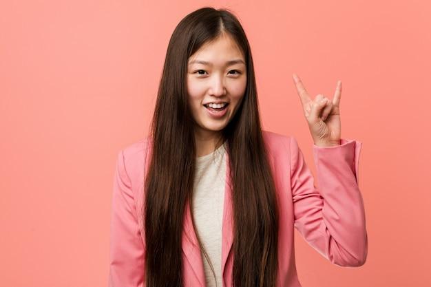 Junge chinesische geschäftsfrau, die den rosa anzug zeigt eine hörnergeste als revolutionskonzept trägt.