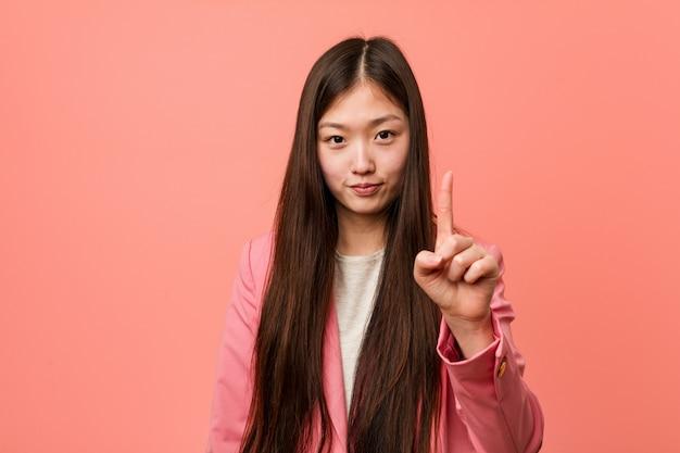 Junge chinesische geschäftsfrau, die den rosa anzug zeigt nummer eins mit dem finger trägt.