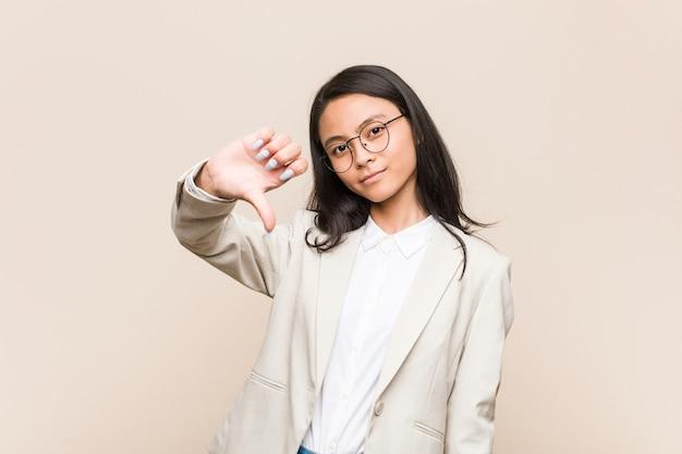 Junge chinesische geschäftsfrau, die eine abneigungsgeste zeigt, daumen nach unten. uneinigkeit konzept.