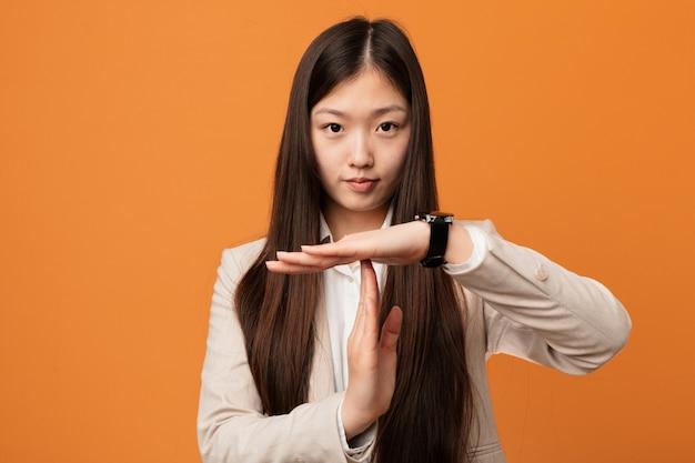 Junge chinesische geschäftsfrau, die eine auszeitgeste zeigt.