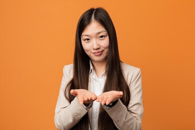 Junge chinesische geschäftsfrau, die etwas mit den palmen, anbietend hält.