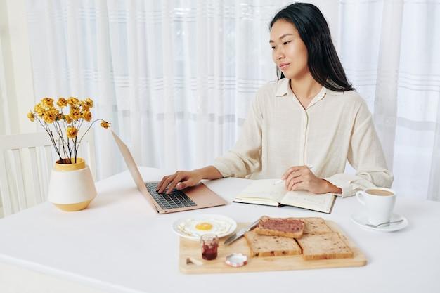 Junge chinesische geschäftsfrau, die frühstück isst, online-kalender prüft und notizen im planer macht