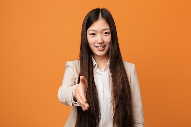 Junge chinesische geschäftsfrau, die hand an der kamera in der grußgeste ausdehnt.
